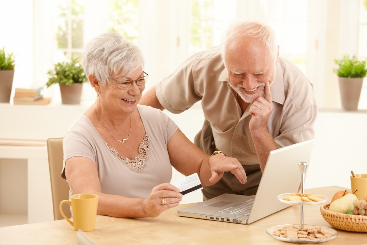 Elderly couple look at laptop